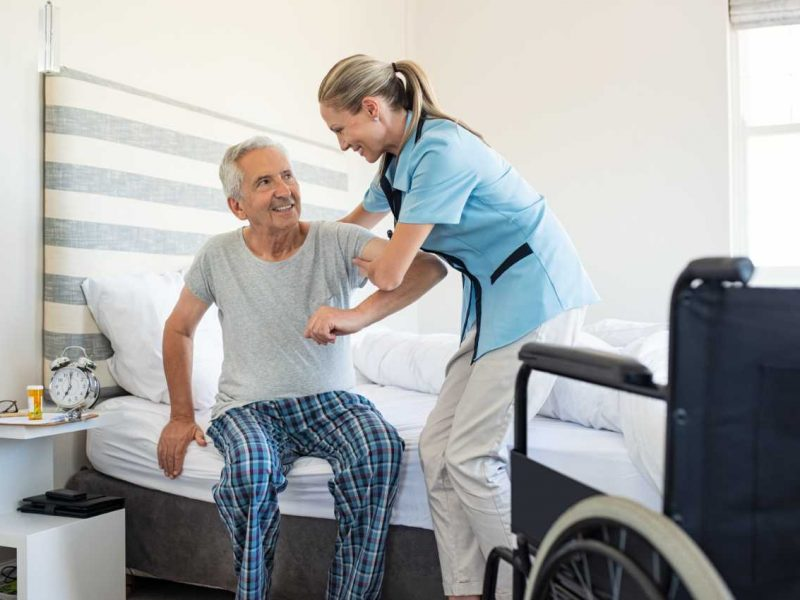 nurse-helping-old-patient-get-up-MJXB65R (1)